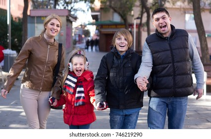 Winter outdoor portrait of ordinary american family with son and daughter