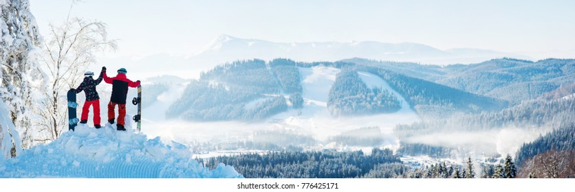 Winter panorama of the Carpathians mountains landscape and forests in a white haze. In the side couple high fiving each other on top of a snowy mountain, resting after snowboarding at ski resort
