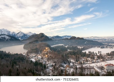 Winter panorama of hazy Hohenschwangau castle with Alpensee Lake at the foot of a Alps mountains. Bavaria, Germany.
