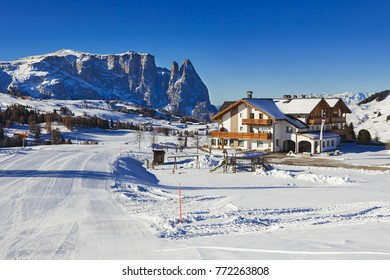 Winter panorama of italian ski resort with background of Seiser Alm, Alpe di Siusi, a high altitude alpine meadow in Dolomites with Langkofel and Plattkofel mountains under snow, South Tyrol, Italy.