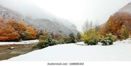 Panorama panorámico invernal con río y nieve rodeado de montañas y árboles marrones y verdes banderas horizontales