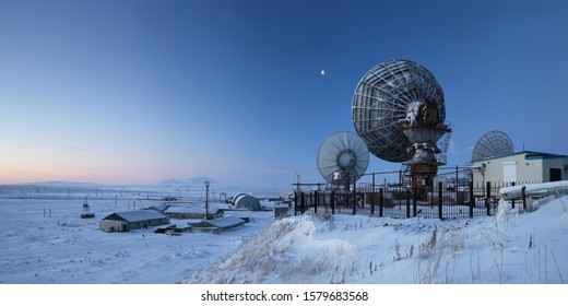 Winter panorama with large satellite dishes. Telecommunications in the Arctic. Industrial landscape with antennas. Morning twilight. Location place: Anadyr, Chukotka, Siberia, Far East of Russia.