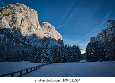 Winter panorama in the valley with sunny mountains on the left and forest in the shadow, Dolomites