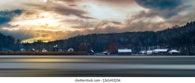 Winter panorama with windmills. Dumbrava lake, Astra Museum of Traditional Folk Civilization, Sibiu city, Romania