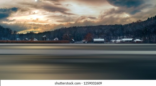 Winter panorama with windmills, the sun through the clouds, and motion blur on lake. Dumbrava lake, Astra Museum of Traditional Folk Civilization, Sibiu city, Romania