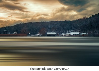 Winter panorama with windmills, the sun through the moody clouds, and motion blur on lake. Dumbrava lake, Astra Museum of Traditional Folk Civilization, Sibiu city, Romania