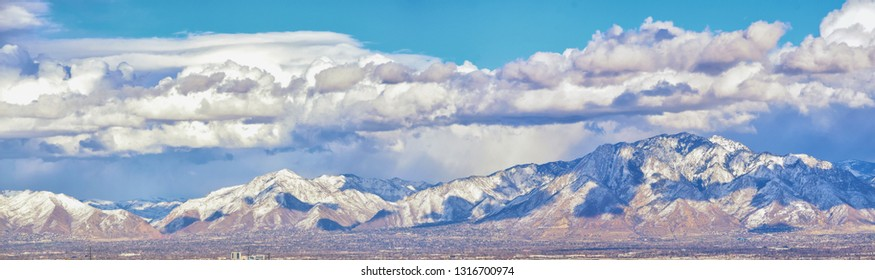 Winter Panoramic view of Snow capped Wasatch Front Rocky Mountains, Great Salt Lake Valley and Cloudscape from the Bacchus Highway. Utah, USA.