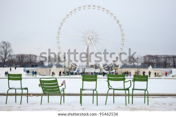 Winter in Paris. Chairs in Tuileries garden and snow