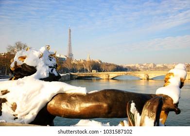Winter in Paris. Closeup of Alexandre III Bridge under snow. View of Eiffel tower at background.