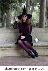 Winter Park, FL / USA - September21 2019: Beautiful Caucasian model dressed as a witch posing on a bench