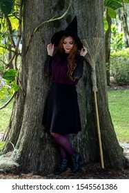 Winter Park, FL / USA - September21 2019: Beautiful Caucasian model dressed as a witch posing next to a tree