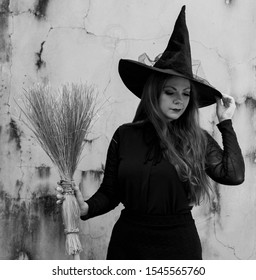 Winter Park, FL / USA - September21 2019: Black and white photo of a beautiful Caucasian model dressed as a witch posing in front of a stone wall