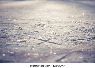 Winter pattern from figure skates on shining ice skating rink with snowflakes as Christmas background