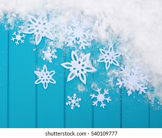 Winter pattern with snowflakes. Blue wood texture with snow Christmas background.