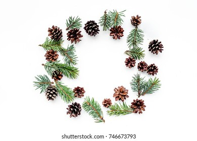 Winter pattern with spruce branch and pinecones on white background top view copyspace