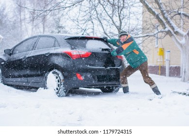 Winter, people and car problem concept. Man are pushing the car, stuck in the snow. Mutual aid. Winter problem. transportation, winter and vehicle concept - closeup of man pushing car stuck in snow