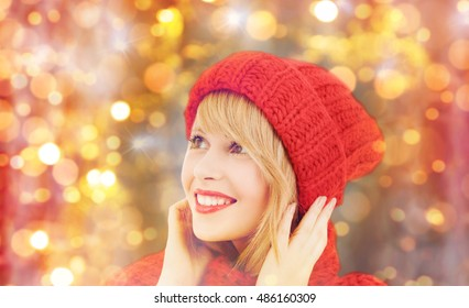 winter, people, christmas and holidays concept - happy smiling woman in red hat and scarf over lights background