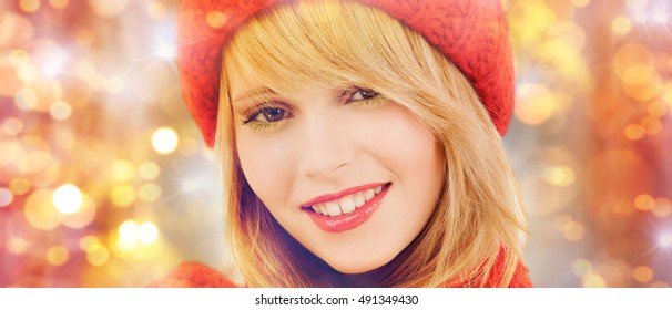 winter, people, christmas and holidays concept - close up of happy smiling woman in red hat and scarf over lights background