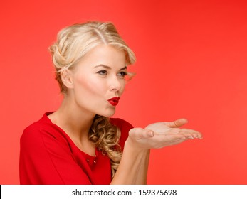 winter, people, happiness concept - happy woman in red dress blowing on palms