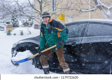 Winter, people and problem concept - closeup of man digging snow with shovel near car and yard. Man standing with blue shovel and he snow cleaning. Winter routine concept.