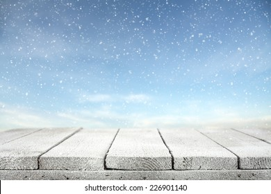 winter photo of blue sky with snow and wooden table