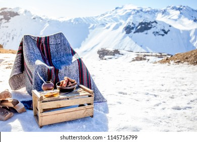 Winter picnic in chilean argentine snow mountaines Andes with hot meat food and drink yerba mate