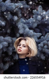 Winter portrait of beautiful blonde girl in the leaves