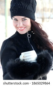 winter portrait of a beautiful blue-eyed brunette. an attractive woman in a black knitted hat with a pompom holds a beige striped Cup in black fur mittens, close-up. smile for a million