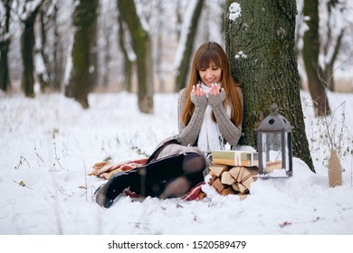 Winter portrait of a beautiful girl in a snowy forest, wrapped in a blanket. Snowflakes on her hair, cold, a beautiful woman warms herself, the atmosphere of winter, it is snowing, a lamp and fire