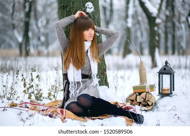 Winter portrait of a beautiful girl in a snowy forest, wrapped in a blanket. Snowflakes on her hair, cold, a beautiful woman warms herself, the atmosphere of winter, it is snowing, a lamp and firewood