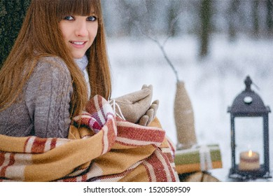 Winter portrait of a beautiful girl in a snowy forest, wrapped in a blanket. Snowflakes on her hair, cold, a beautiful woman is warming herself, the atmosphere of winter, it is snowing, a magic