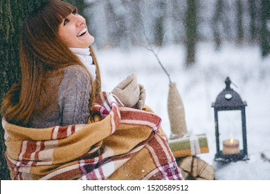 Winter portrait of a beautiful girl in a snowy forest, wrapped in a blanket. Snowflakes on her hair, cold, a beautiful woman is warming herself, the atmosphere of winter, it is snowing, a magical