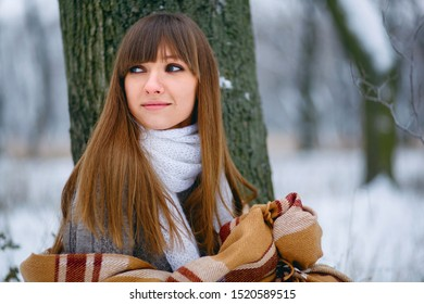 Winter portrait of a beautiful girl in a snowy forest, wrapped in a blanket. Bare head, snowflakes on hair, cold, beautiful woman is warming, winter atmosphere