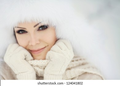 Winter portrait of beautiful smiling woman with snowflakes in white furs