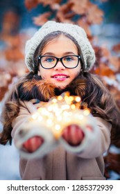 Winter portrait of a beautiful young girl in knitted beret and beige coat . Tenderness positive child with bright smile enjoying nature in snowing park with lights.