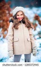 Winter portrait of a beautiful young girl in knitted beret and beige coat . Tenderness positive child with bright smile enjoying nature in snowing park.