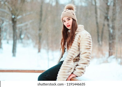 winter portrait of beautiful young woman in fur coat and knitted hat walking in snowy park or forest.