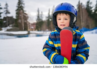 Winter portrait of a cute little Caucasian boy wearing ski helmet and holding his skis