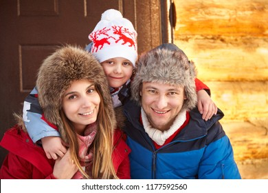 winter portrait of a family in the winter outdoors near a house