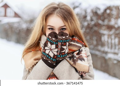 Winter portrait of a girl hiding in her scarf on the background of the village.