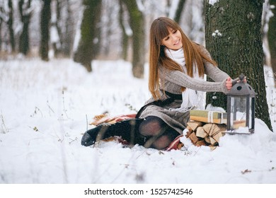 Winter portrait of a girl in a snowy forest, wrapped in a blanket. Naked head, snowflakes on her hair, cold, beautiful woman is warming, the atmosphere of winter, it is snowing, the girl is warming h