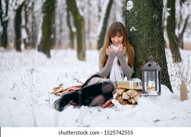 Winter portrait of a girl in a snowy forest, wrapped in a blanket. A naked head, snowflakes on her hair, cold, a beautiful woman warms herself, the atmosphere of winter, it is snowing, a lamp and fir