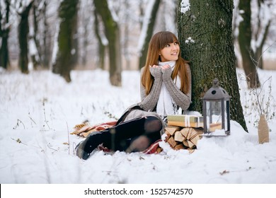 Winter portrait of a girl in a snowy forest, wrapped in a blanket. A naked head, snowflakes on her hair, cold, a beautiful woman warms herself, the atmosphere of winter, it is snowing, a lamp and fire