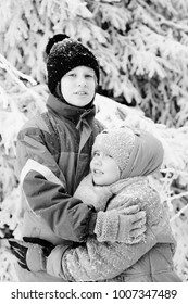 Winter portrait of happy 7 years old girl with her autistic 10 years old brother outdoors