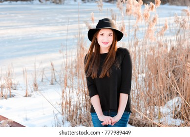 Winter portrait of a happy beautiful girl with brown hair in winter forest on the lake. Woman wearing a hat and bright clothes. Winter atmosphere, nature and freedom concept.