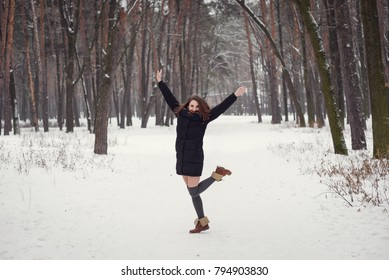 Winter portrait of a happy beautiful girl with brown hair in snow winter forest . Woman wearing knitted grey pullover dress and stockings high socks. Winter atmosphere, nature and freedom concept.
