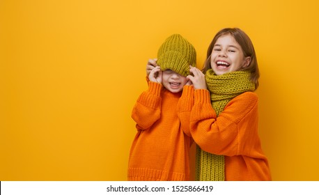 Winter portrait of happy children wearing knitted hat, snood and sweaters. Girls having fun, playing and laughing on yellow background. Fashion concept.