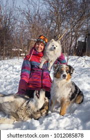 Winter portrait of happy girl and her cute three dogs - malamute, Aussie and Japanese spitz. Almaty region, Kazakhstan.