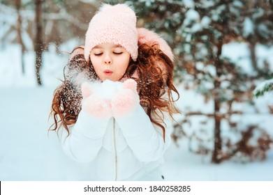 Winterporträt von glücklicher Junge Mädchen in weißem Mantel und Hut und rosafarbene Fingern spielen draußen im schneebedeckten Winterwald und blasen Schnee. Glückliche Kindheit und aktive Winterferien-Konzepte