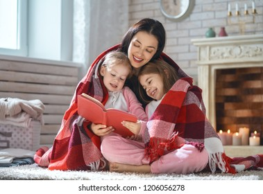 Winter portrait of happy loving family. Pretty young mother reading a book to her daughters at home.